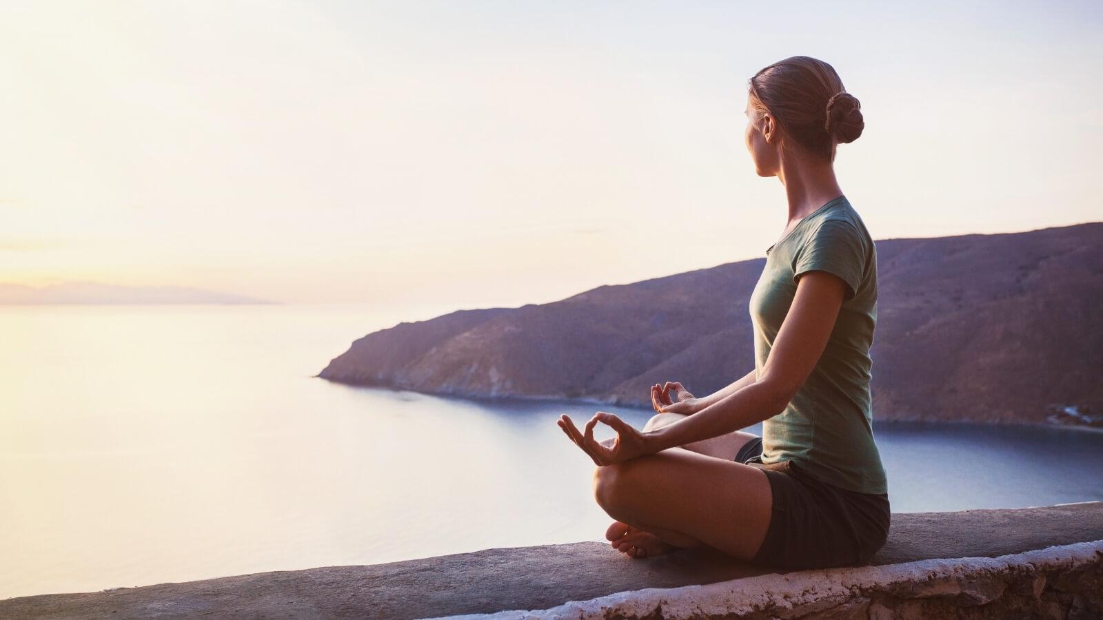 Frau macht Yoga am Meer - Meditation lernen