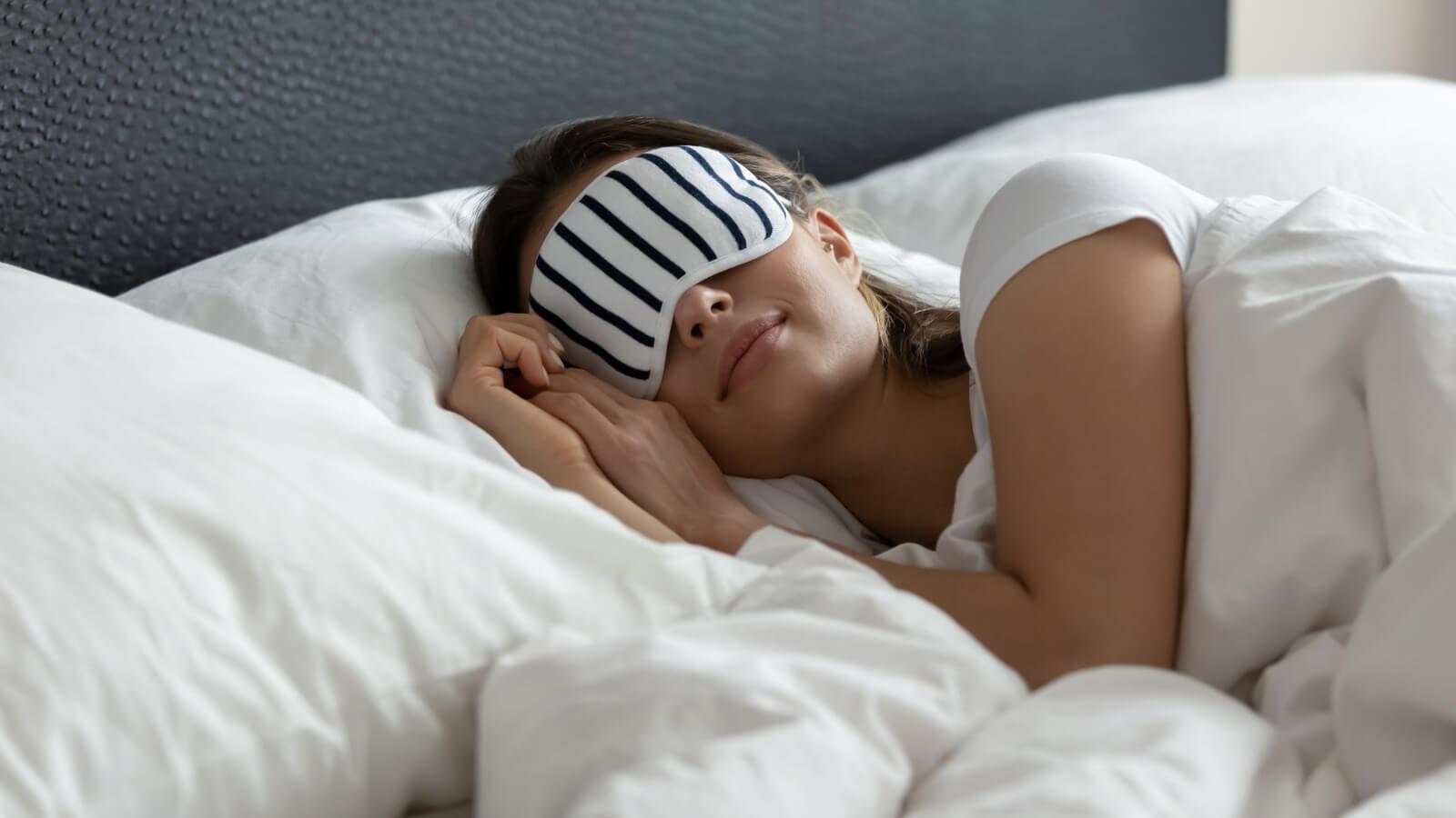 Eine Frau mit Schlafmaske liegt in einem Bett und schläft.