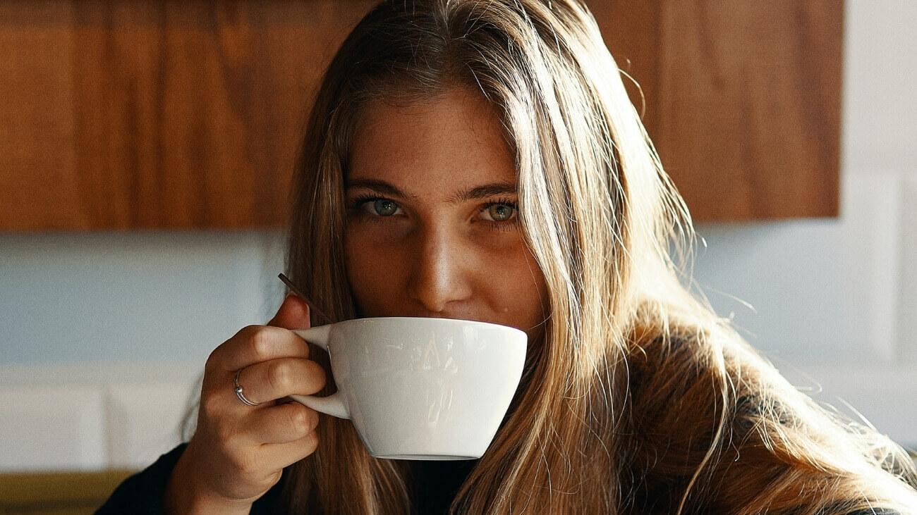 Frau trinkt Kollagen-Kaffee aus einer Tasse - Kollagen Rezepte